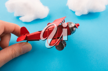Retro styled red model airplane in hand, blue sky and clouds
