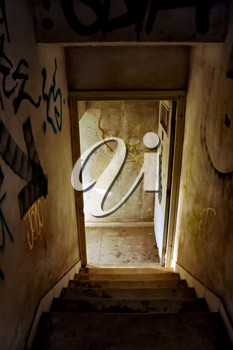 Staircase and exit door of an abandoned house.