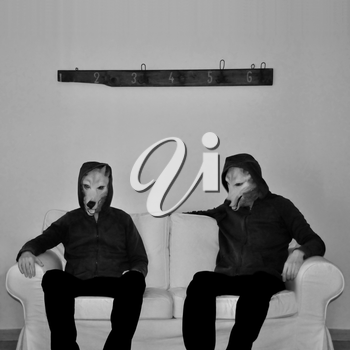 Two figures with dog mask sitting on couch. Black and white.