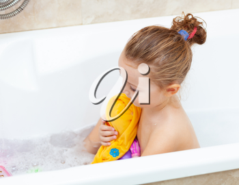 Cute adorable baby girl taking foamy bath in bathtub. Toddler playing with bath rubber toys. Beautiful child having fun with colorful plastic toys and foam bubbles.