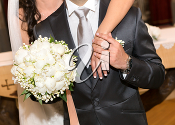 Married couple with bouquet of white peonies.