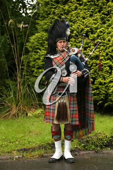 EDINBURGH, SCOTLAND - JULY 28 2015 : Unidentified Scottish Bagpiper playing music with bagpipe in Scotland.  Bagpipes are a class of musical instrument, aerophones, and have been played for centuries.